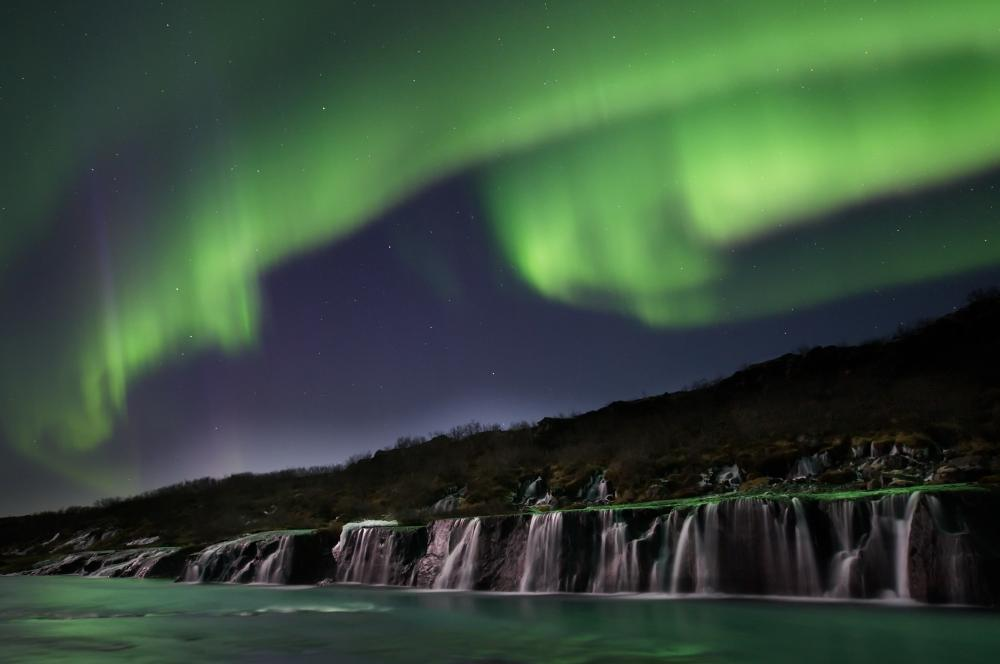 Northern lights over Hraunfoss waterfall close to Vinheimar cottage, click to book!